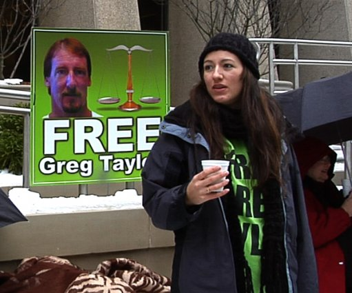A woman stands in front of a 'Free Greg Taylor' poster.