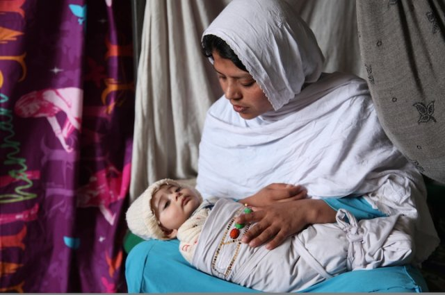 A woman in Hijab is holding her child.