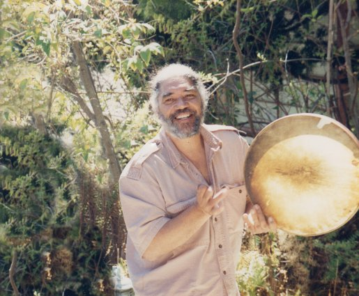 Bruce stands holding a drum before a forest.