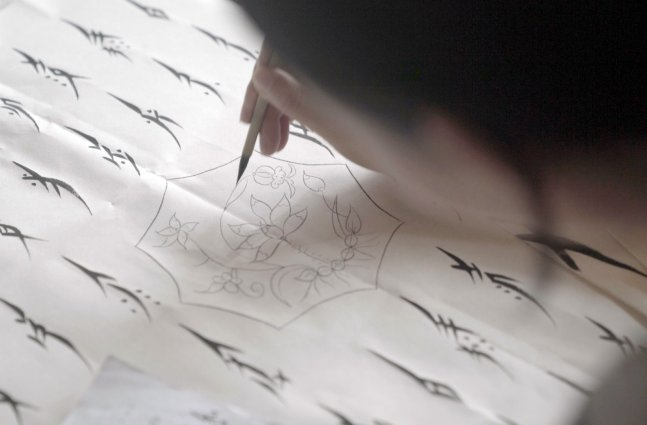 Hu xin writes Nushu characters with a small paint brush.