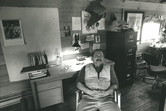 Jim Harrison sits with his hands in his lap in his rugged, outdoorsy 20th-century office.