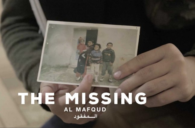 a person in a thick jacket holds up a photograph of four children in front of an old building