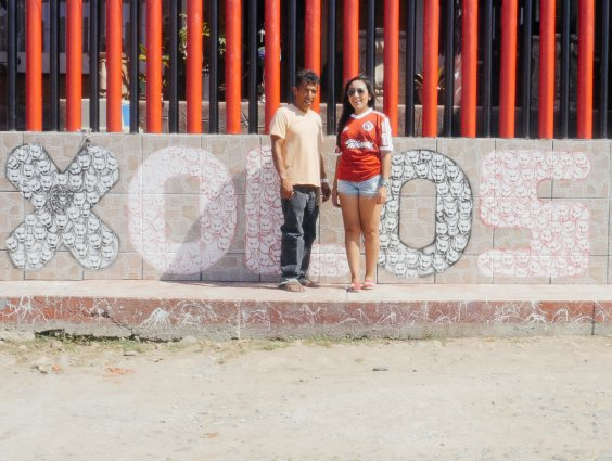 Two people are standing in front of a wall that has 'xolos' graffitied on it.