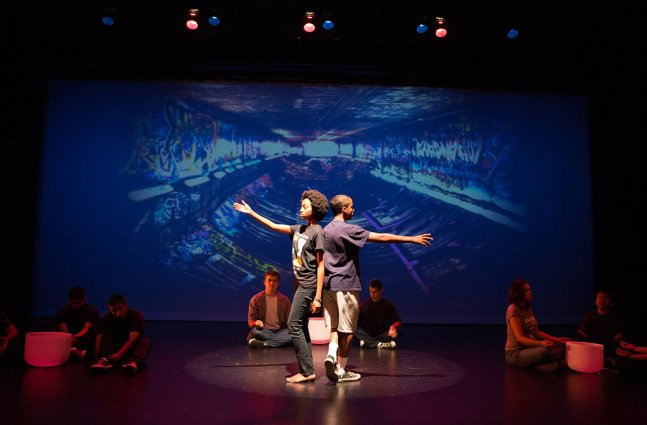 Two young Black teenagers stand back-to-back with a single arm stretched out in opposite directions. They stand under a spotlight on stage in front of a projection screen showing a graffitied pipeline. Several other students sit on the stage around them, sitting next to sound bowls.