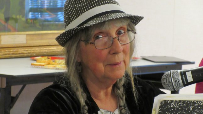 An older White woman in glasses and hat reads from a composition book before a notebook.