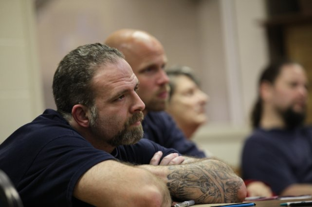 middle aged white male convict listens with arms crossed at a re-entry training