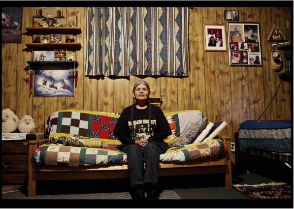 Native American women sits on a quilted couch with her hands in her lap in her wooden house