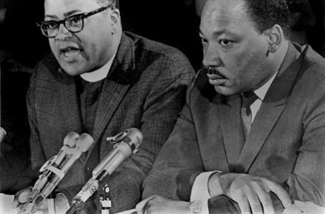 Reverend James Lawson sits and speaks next to Martin Luther King Jr.