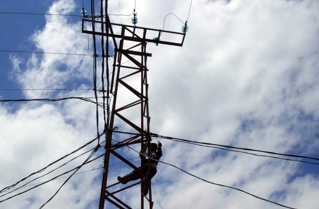 line worker works on electric tower in the Congo
