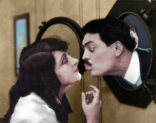 Max Linder is kissing a woman in a movie scene.