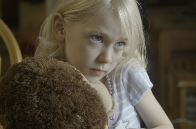 Transgender child and main subject of Mama Bears holding a stuffed toy.