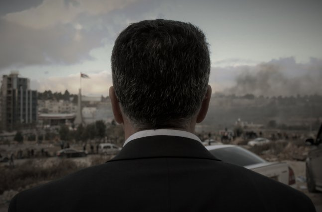 Main subject of film looks away from camera towards his town in a suit.