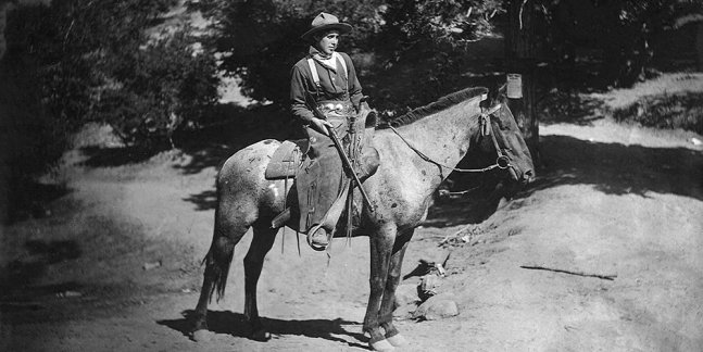 A 19th century cowboy on horseback with a rifle.