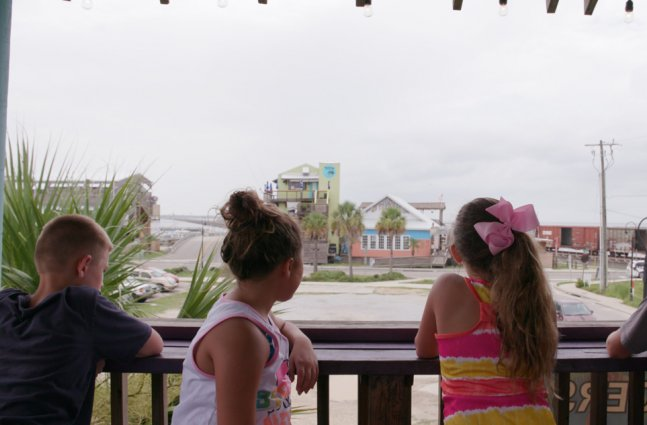 two young boys and two young girls stare away from camera looking onto a Mississippi street.