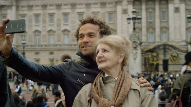 Sian-Pierre and his mom are taking a selfie in a European city.