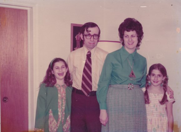 A late-20th century family photo with Mom and Dad in the middle and two daughters on either side.