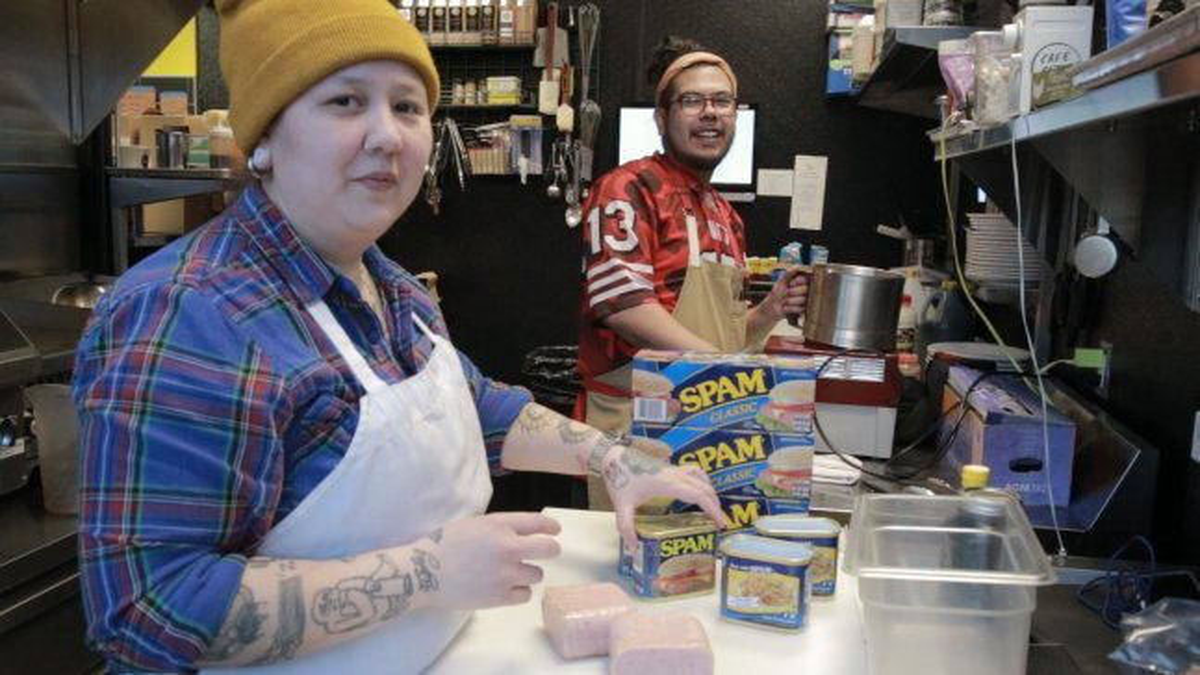 Two Filipino-American are preparing dishes in the kitchen.