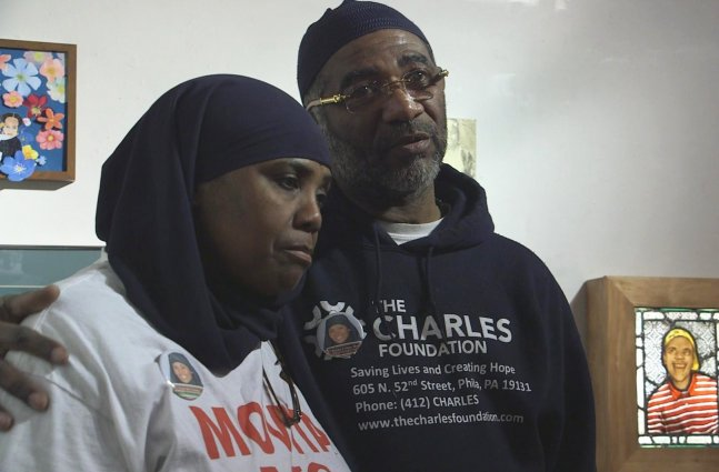"""A still from """"Murders That Matter"""": Protagonist Movita Johnson-Harrell, a middle-aged Black woman in a white t-shirt and black hijab, stands next to a middle aged Black man wearing a blue hoodie that says """"The Charles Foundation"""""""