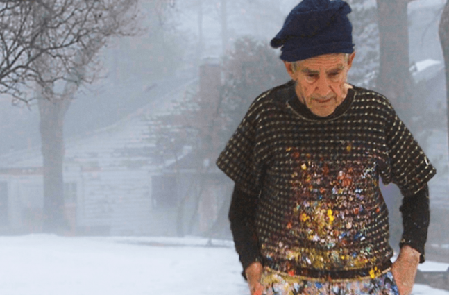 an older White Man with a paint-splattered sweater and knit cap stands in front of a snow-covered house.