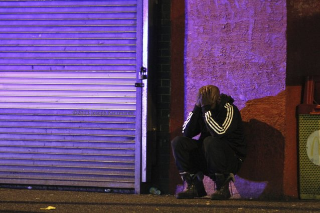 A Black Man in a track suit leans against a city strip wall with his head in his hands