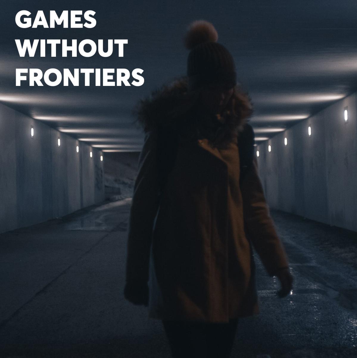 An unidentifiable man stands in a dark hallway underground.
