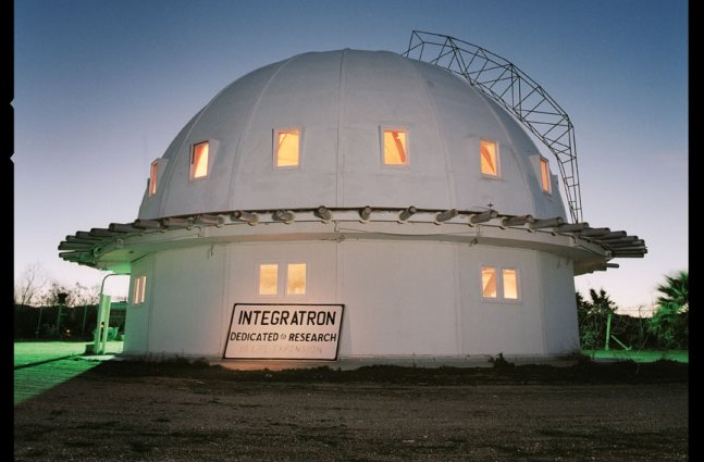 A white dome research center sits on a green lawn at dusk with stars shining in the sky above