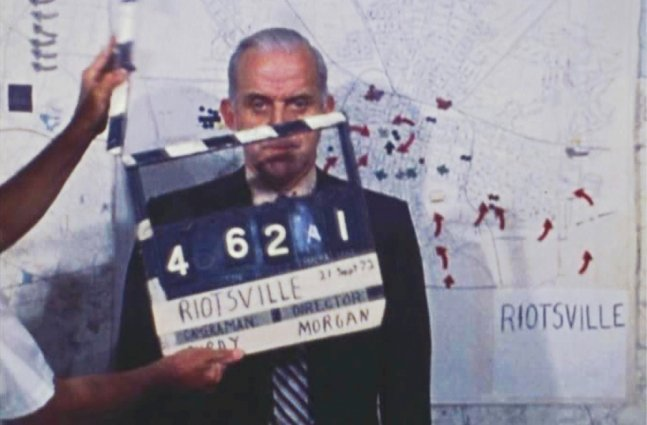 white male standing behind clapper board and in front of map labeled Riotsville with marked locations