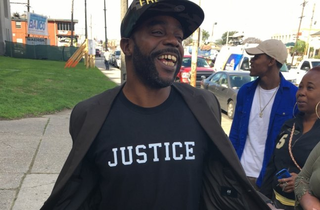 """Black male smiles at bystanders as he shows his t-shirt with the word """"Justice"""" on it."""