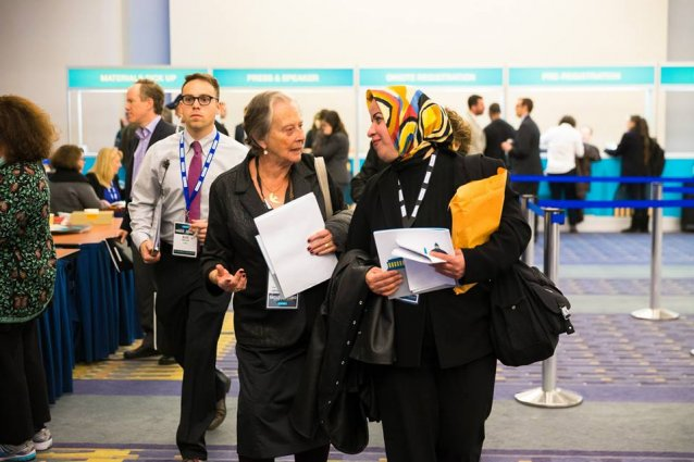 Two women are talking while walking away from a booth in a conference.