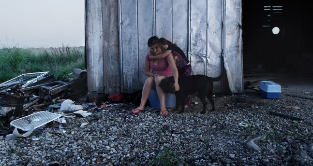 two female siblings sit on a plastic box and pet their black dog in front of a rural dilapidated barn.
