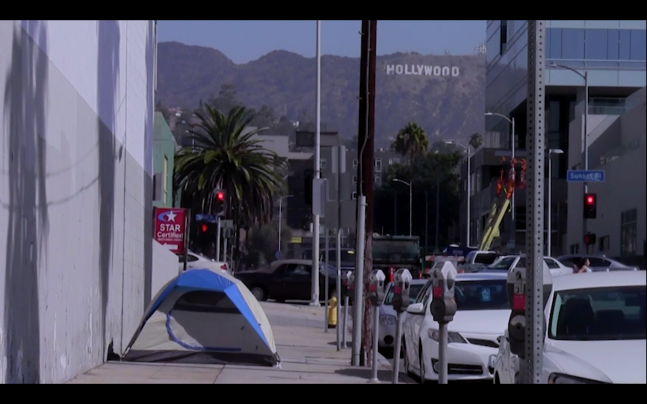 The tent of an unhoused person on the street with the hollywood sign in the background.