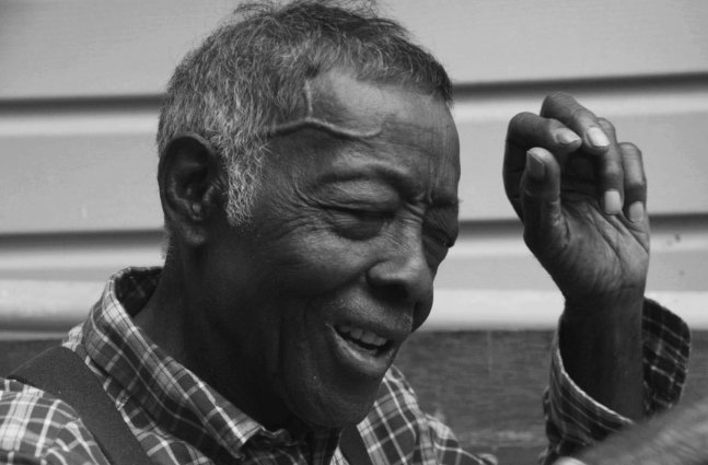 A black & white image of an elderly man of African-American descent sitting on a porch.