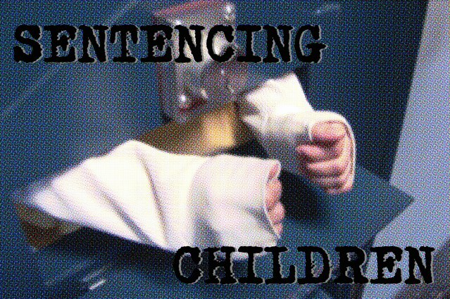 the arms of child reach through the prison door grate, ready to be handcuffed.