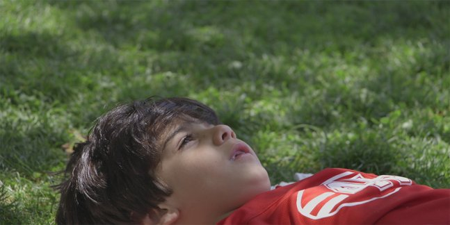 Young Iranian boy lays on the grass looking up at the sky.