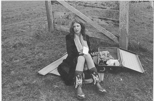 Young woman in early 70's fashion sits on a picnic blanket next to an open suitcase with a notepad in her hand.