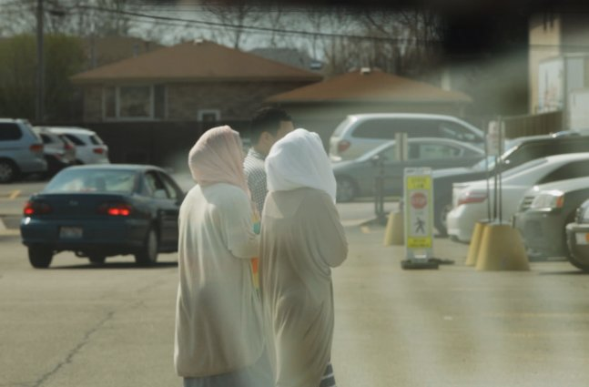two women dressed in traditional muslim attire walk through parking lot with male