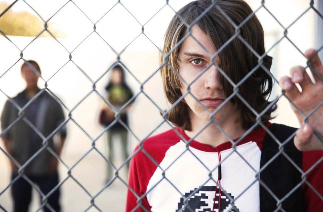 white male teen looks through chainlink fence at school