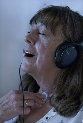 A middle-aged white woman with blue headphones closes her eyes as she adjusts a voicebox on her neck.