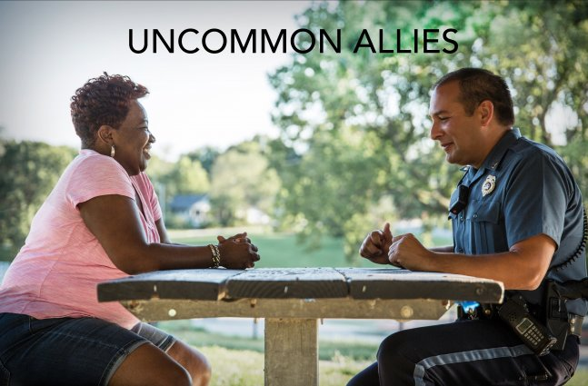 A Black woman sits across a park picnic table from a White Cop in uniform