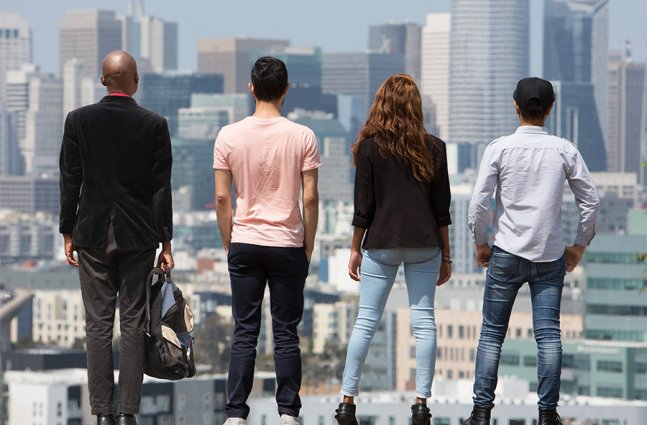 4 individuals looking out at LA skyline.