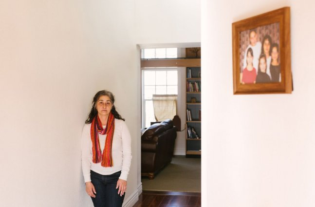 Jessica Gonzales Lenahan stands to the left of a doorway in their home with a family portrait on the right wall