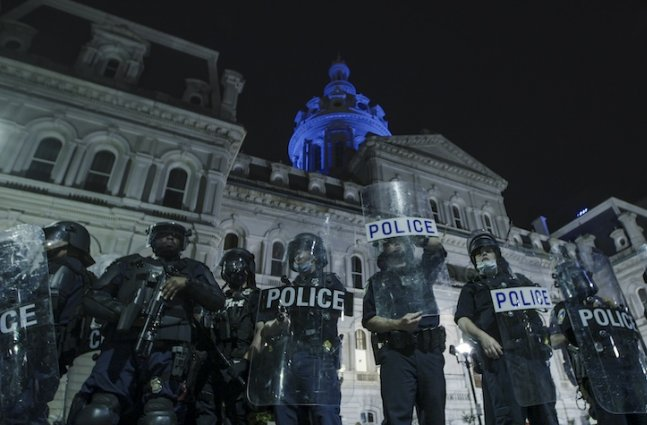 A line of Baltimore police officers wearing riot gear and holding shields stand in front of city hall the night after the murder of George Floyd.