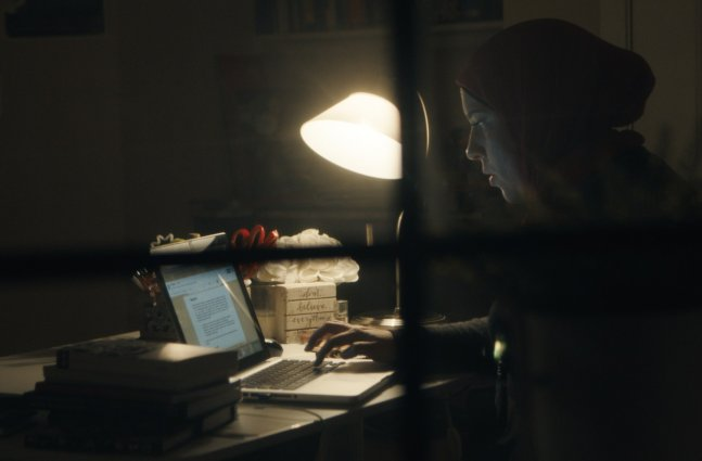 A woman in a hijab working at her computer late into the night, slightly obscured by a windowpane in the foreground.