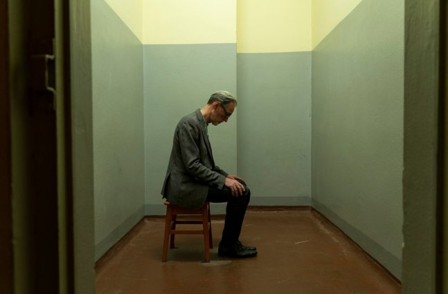 A man sitting in an empty small room looking down at his feet