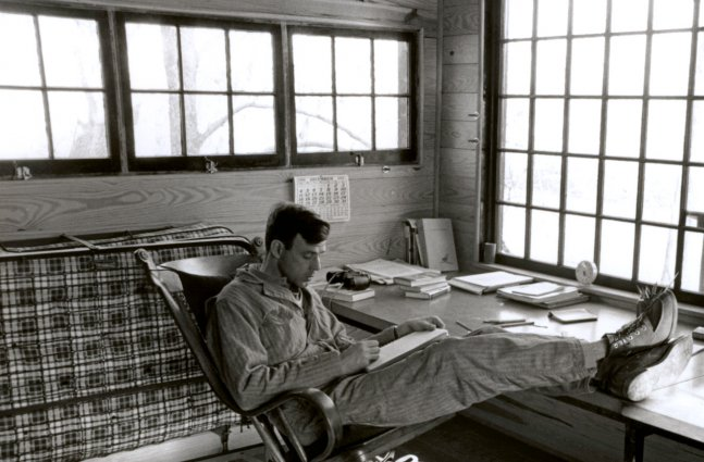 a black and white image of Wendell Berry reading a book in a chair with feet kicked up on table