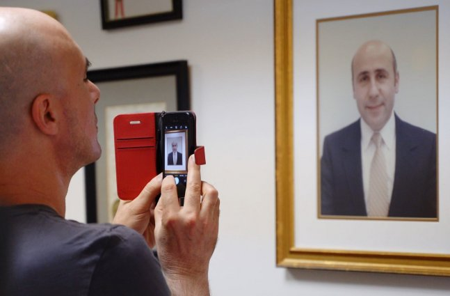 Bald white man takes a photo with an iPhone of a framed portrait of Alex Odeh.