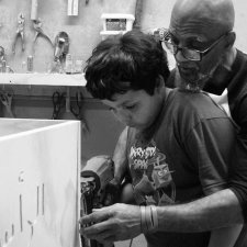 :A  bald Black man with glasses teaches a young boy with black hair how to engrave a casket with a drill.