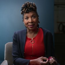 KIMBERLÉ CRENSHAW, Professor, UCLA and Columbia Schools of Law. She is an African-American woman, wearing a red blouse under a navy blue blazer; she is seated against a blue backdrop. From episode 3 of 'AMEND-The Fight for America.' Credit: Courtesy of Netflix/NETFLIX©2021