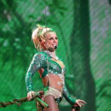 """Pop star Britney Spears, subject the recnt documentary 'Framing Britney Spears,"""" is pictured performing on stage, wearing an emerald green sequin outfit, singing into a wireless headset, clutching a brown railing, against a mesh, emerald green patterned backdrop."""