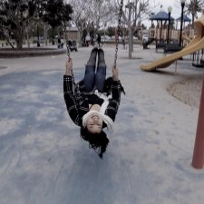 A woman from the film swings on  a swing in the middle of a playground; her head is upside-down as she faces the camera.